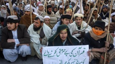 A supporter of the Jamaat-ud-Dawa Islamic organisation holds a placard while taking part in an anti-US rally in Quetta.