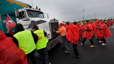 Body on the line ... A worker jumps in front of a truck in a bid to stop it crossing the picket line at Somerton yesterday.