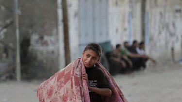 A Palestinian boy flees his house in Jebaliya refugee camp in the northern Gaza Strip on Tuesday.