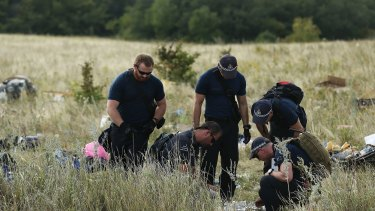 Australian Federal Police officers and their Dutch counterparts collect human remains from the MH17 crash site.
