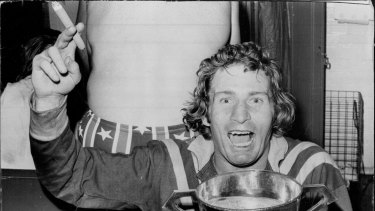 Graeme Langlands, with a cigar in his hand and the Ashes Cup full of champagne in the other, relaxes in the dressing room after leading Australia to their 22-18 win in the third Rugby League Test at the SCG on July 20, 1974.