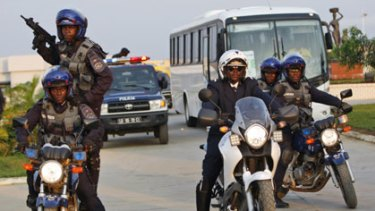 High alert...police escort the Ivory Coast team from their compound in Cabinda.