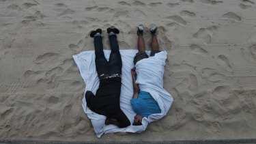 The morning after ... two revellers sleep it off on the beach.