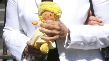 Lisa Harnum's mother, Joan Harnum, carries a doll, believed to have belonged to her daughter, at the NSW Supreme Court as the judge hands down her decision in the murder trial of Simon Gittany.