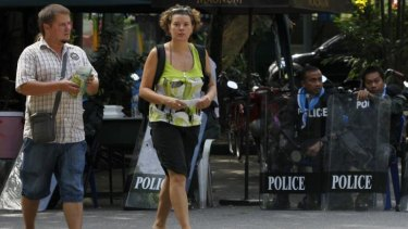 Walk this way: Tourists walk past riot policemen at Dusit Zoo in Bangkok in late November. The tensions continue.