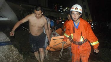 An injured passenger is carried from the wreckage.