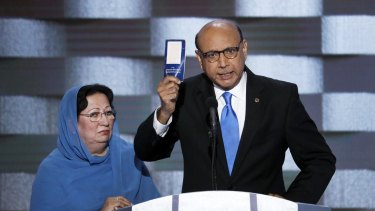 Khizr Khan, father of fallen US Army Captain Humayun Khan, holds up a copy of the US constitution at the Democratic National Convention as his wife Ghazala listens.