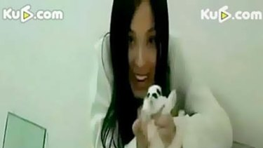 A young Chinese woman holding a baby rabbit before covering it with a plate of glass and sitting on it to kill it.