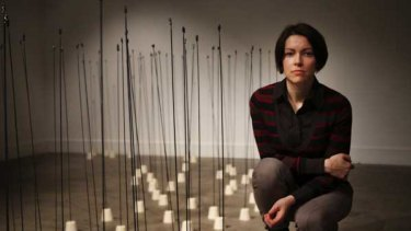 Dorota Mytych and her installation. At the top of each rod is a clay sculpture of a human.