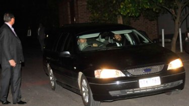 Security guards surround a hearse containing Richard Pratt's body as it is taken by rabbis from Raheen tonight.