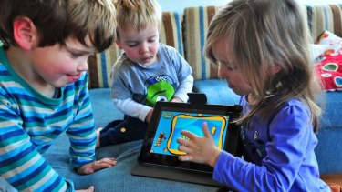 The Marshall children Robbie (3), Nicolas (2) and Milli (5) with their electronic devices.