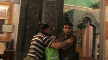 """""""You are a terrorist"""" ... a security guard, left, scuffles with a Palestinian man during the visit of Middle East envoy Tony Blair to the Ibrahimi mosque in the West Bank city of Hebron."""