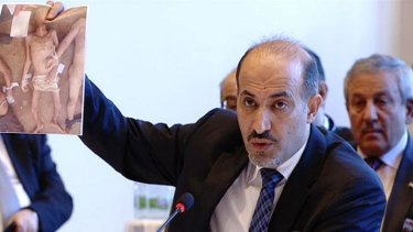 Syrian opposition leader Ahmad al-Jarba holds up recently released pictures that purport to show deaths in Syrian regime custody at the talks in Montreux on Wednesday.