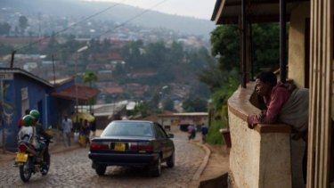 Slowly rebuilding their lives: A woman stands on her porch at a suburb set on a hill overlooking Kigali, Rwanda's capital.