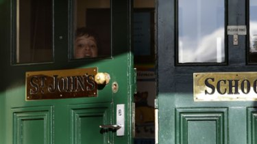 Wes Cretella looks through the front doors of St John's Catholic Primary School in Clifton Hill, the latest school hit by swine flu.