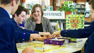 Thrill of the game: Year 9 students from Waverley College, from left, Daniel Keneally, Sam Hodge and Harrison Kyriakou play a new board game invented by Andrea Thompson, pictured.
