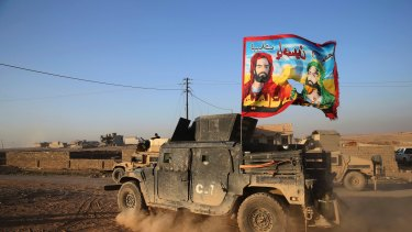 An Iraqi special forces vehicle carries a Shiite flag near Mosul in November.