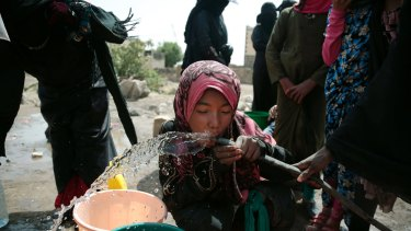 A girl drinks water from a well believed contaminated with the bacterium Vibrio cholera, on the outskirts of Sanaa.