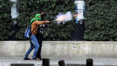 A Muslim Brotherhood supporter aims fireworks at supporters of the Egyptian government in Cairo.