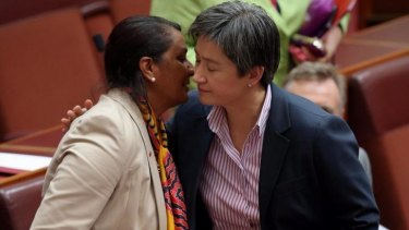 Senator Nova Peris is embraced by Opposition Leader in the Senate Penny Wong following her statement.