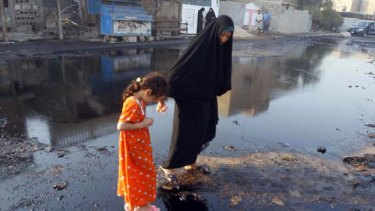 An Iraqi girl is helped by a relative as they walk on spilled oil at the spot where a fuel truck exploded in the Iraqi capital's Ur district. <i>Picture: AFP</i>