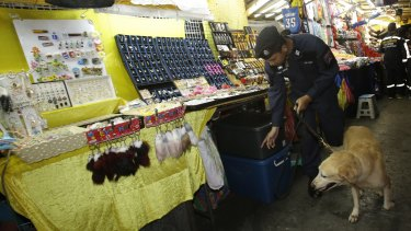 A Thai policeman patrols with a bomb-sniffing dog at a night market in Bangkok last month.
