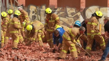 Firemen and workers with bare hands frantically dig into the fallen brick wall in Swanston Street in 2013.