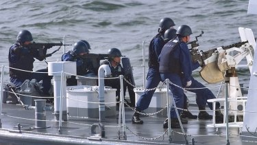 Members of Japan's Maritime Safety Agency aim their guns during an exercise against smugglers.