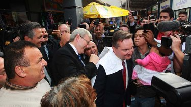 Hero worship: Kevin Rudd signs autographs for his followers in Fairfield in western Sydney this week using Chris Bowen's back.
