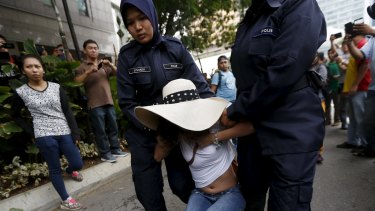 Police seize a demonstrator in Kuala Lumpur.