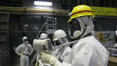 An official of Tokyo Electric Power Co measuring radiation at the Fukushima nuclear plant.