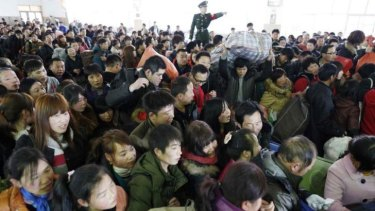 A policeman tries to control passengers at a railway station in Hangzhou, Zhejiang province.