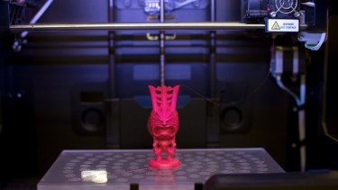 A figurine is constructed in a Makerbot printer.