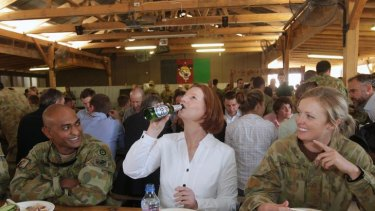 Prime Minister Julia Gillard drinks a Beck's Non-Alcoholic beer offered to her by Sergeant Vernon Pather (left) as Private Emily Smyth (right) looks on, during a BBQ lunch at the Multi-National Base in Tarin Kowt, Afghanistan.