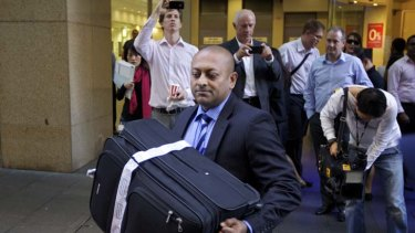 Evidence ... Detective Sergeant Ronald Prasad removes a suitcase Michael Williamson had used from the Sydney offices of the Health Services Union yesterday.