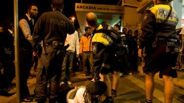 High profile ... police apprehend a man as tension boil over in Harris Park last night.