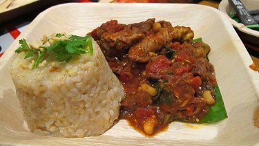 Spicy goat stew with black eye beans, spinach and rice.