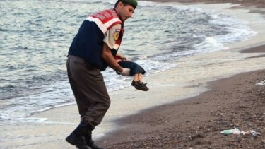 A police officer carries Aylan Kurdi after he washed up on a beach near the Turkish resort of Bodrum.