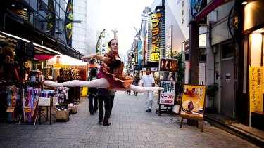 Quirky appeal: A dancer shows off her aerial skills in a Tokyo market.