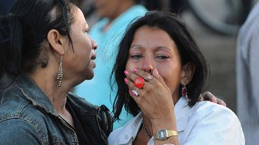 Hundreds dead ... a woman weeps outside the prison.