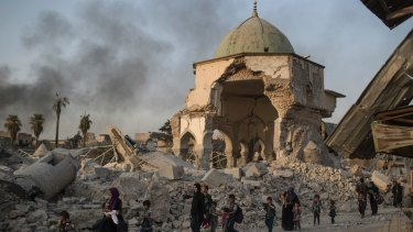 Fleeing Iraqi civilians walk past the heavily damaged al-Nuri mosque in the Old City of Mosul.