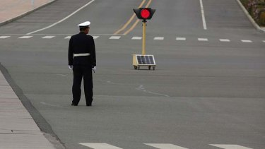 A policeman monitors an empty intersection.