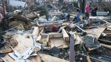 Residents search through debris following the likely tornado touch down in Gifford, Illinois.