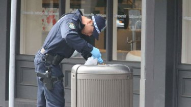 A police officer searches bins near the site of the explosion in Rozelle.