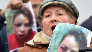 Protesters hold photos of journalist Tetyana Chornovil during a picket at the Internal Affairs Ministry in Kiev.