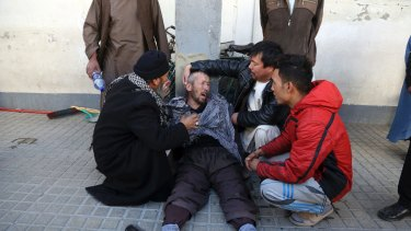 A distraught man is cared for outside a hospital following a suicide attack in Kabul, Afghanistan, on Thursday.