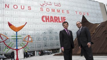 French President Francois Hollande (right) and the President of the Institut du Monde Arabe (Arab Institute), Jack Lang pose in front of the Arab Institute building bearing the message 'We are Charlie', in Paris.