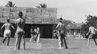 Australian soldiers playing cricket on an improvised wicket in Malaya, 1941.