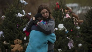 Siblings hug in front of a row of Christmas trees, which line the street near Sandy Hook Elementary School.