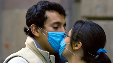On alert ... a couple wearing masks kiss in Mexico City.